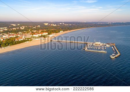 Sopot resort in Poland. Wooden pier (molo) with marina, yachts, pirate tourist ship,  beach, town, vacation infrastructure, hotels, park and promenade. Far view of Gdynia.  Aerial view at sunrise.