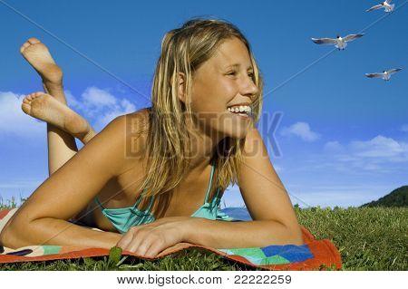 beautiful woman with bikini lying on a meadow.