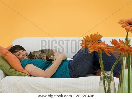 young woman sleeping on a sofa with a little cat