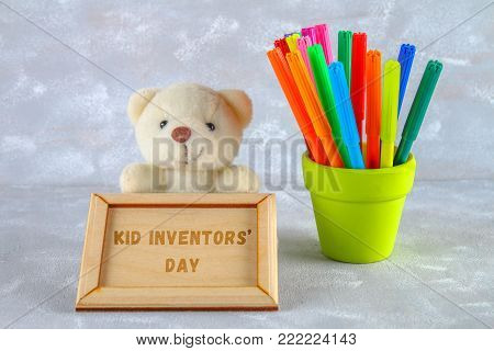 Teddy bear, markers, plaque and drawings of children's inventions - popsicles, Earmuffs, calculator on a gray background. Text - Kid Inventors' Day