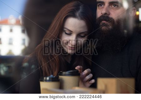 Happy, in love couple, of two hipsters, young woman and middle aged bearded man, cuddle and hug in cafe window. Drink coffee from take away cups and show affection and tenderness
