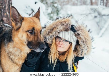 Best friends, young blond woman in winter jacket and hat, stands next to her pet friend a big german shepherd dog. Animal protection day and love for animals