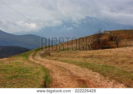 The dirt road in mountains. Twisty road on a mountain plateau in Crimea in cloudy day.