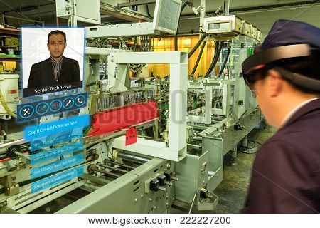 iot smart industry 4.0 concept. Industrial engineer(blurred) using smart glasses with augmented mixed virtual reality technology to contact senior technician and receive an advice to fix the machine