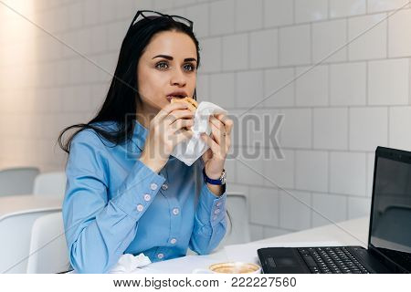 hungry young girl student in blue shirt having dinner in cafe after lectures at university