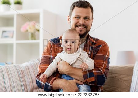 family, parenthood and people concept - happy father with little baby boy at home