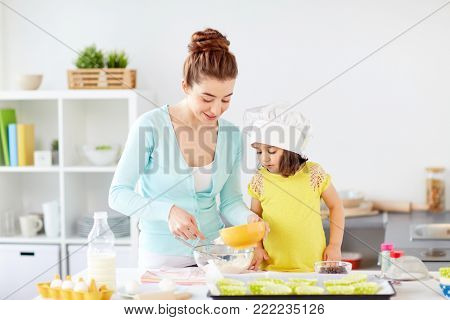 family, cooking, baking and people concept - happy mother and little daughter in chefs toque making batter for muffins at home kitchen