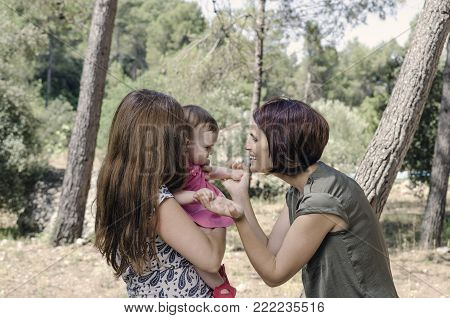 Portrait Of Happy Lesbians Mothers With A Baby.  Homosexual Family In A Countryside.