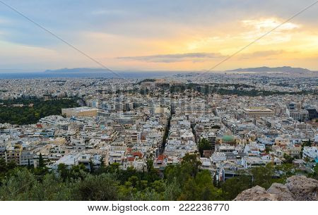 Evening cityscape of Athens, with the Acropolis seen in the background at sunset.