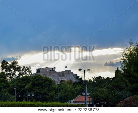 The ancient citadel Acropolis of Athens with the flying flag of Greece.
