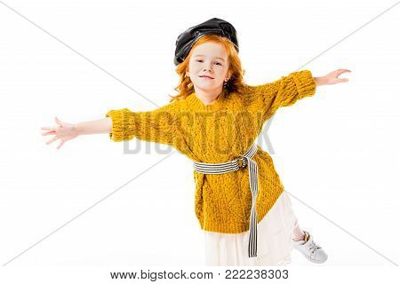 red hair child standing on one leg with open arms isolated on white