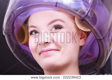 Beautiful young woman in beauty salon. Blond girl with hair curlers rollers. Modern equipment by hairdresser. Hairstyle.