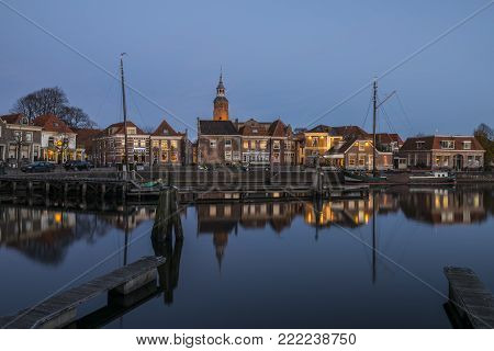 Blokzijl, The Netherlands - November 24, 2016: The harbor with two flat bottoms (ships) of Blokzijl in the province of Overijssel. With old monumental houses and church.