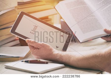 Man sitting in a library and holding in hands a modern ebook reader and paper books in the background