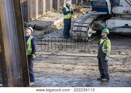 Driebergen, Netherlands - November 26, 2017: Construction site at the railway station in Driebergen, province Utrecht, with crane and three workers.