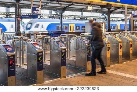Nijmegen, Netherlands - November 7, 2017: OV-gates at railway central station Nijmegen with travellers and trains at the platform.