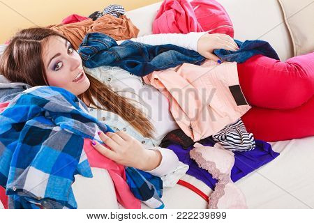 Happy woman lying on sofa couch in messy living room. Young girl surrounded by many stack of clothes. Disorder and mess at home.