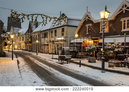 Wijk bij Duurstede, Netherlands - December 11, 2017: Shopping street in december during Xmas and winter with shops and snow.