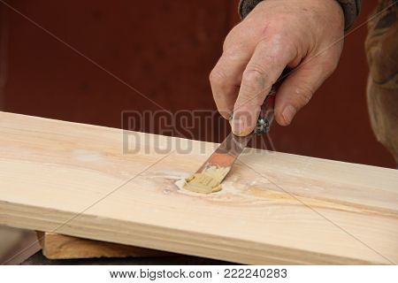 Putty knife in old man's hand. Removing paint from a wood surface. Preparation of boards before impregnation with varnish. Application of putty. Copy space for text.