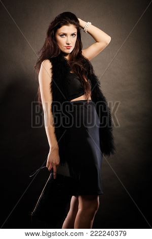 Party celebration carnival concept.  Magnificent long hair woman wearing black evening dress feather boa holds handbag in hand on dark