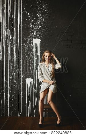 Beautiful fashionable half-naked brown-haired woman in the sits in front of dark background.