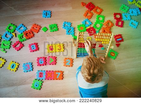 little boy learn numbers - calculation on abacus, playing with number puzzle