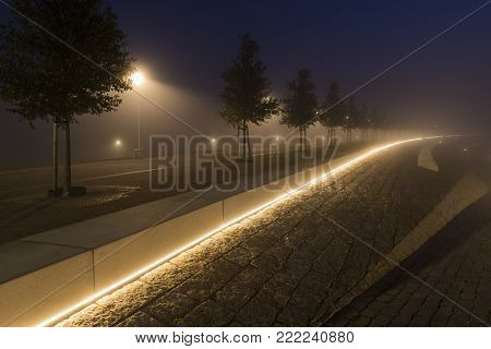 Modern dike in Nijmegen in the morning with streetlights, trees and fog, Netherlands.