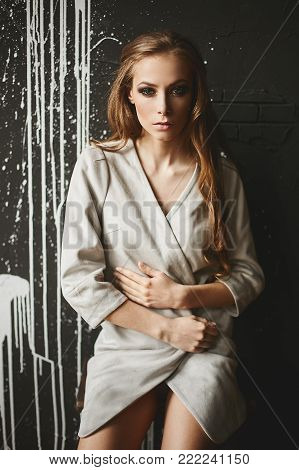 Beautiful fashionable half-naked brown-haired woman in the jacket pose in front of the dark wall.