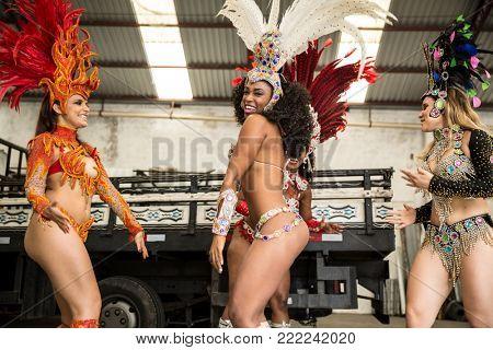 Brazilian women dancing samba music for the carnival in an old factory