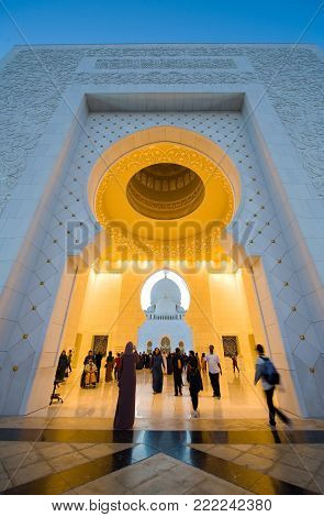 ABU DHABI, UNITED ARAB EMIRATES - DEC 31, 2017: The main entrance in twilight of the Sheikh Zayed Mosque in Abu Dhabi. It is the largest mosque in the country.