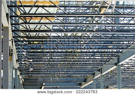 A ceiling of steel girders weigh heavily on the space below.