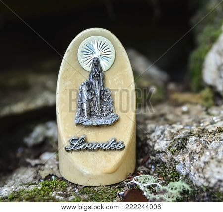 The statue of Our Lady of Lourdes on ivory stone