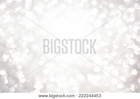 Silver white glittering Christmas lights. Blurred abstract background with flying hearts, Valentine's day wallpaper