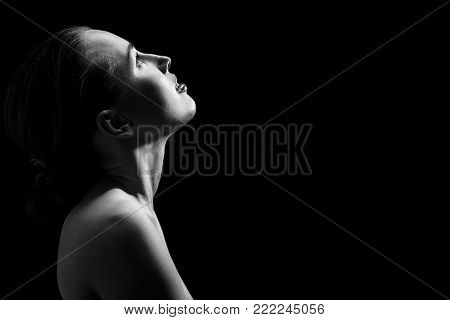 sensual aroused woman looking up on black background, monochrome
