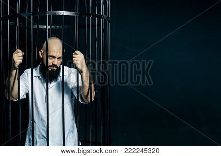 Depressed male inmate holds prison bars in despair. Fashion concept over black background. Copyspace
