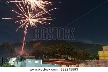 PANAJACHEL, GUATEMALA - JANUARY 1: News years eve celeration fireworks over rooftops on January 1, 2018 in Panajachel, Solola.