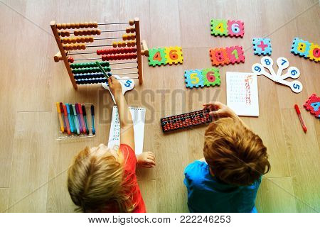 cute little boy and girl learning numbers, mental arithmetic, abacus calculation