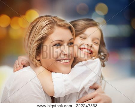 family and motherhood concept - happy mother and little daughter hugging over holidays lights background