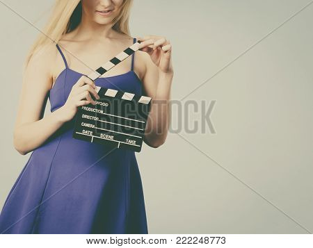 Woman holding professional film slate, movie clapper board. Hollywood production objects concept.
