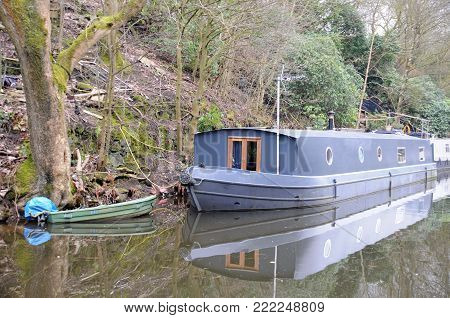 grey barge houseboat with green rowing boat moored on the rochdale canal near hebden bridge