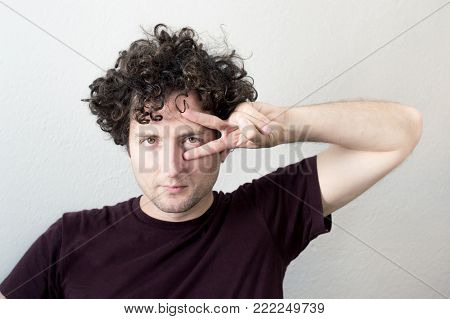 Portrait of a young, Caucasian, brunet, curly haired man with pensive expression on a white background.