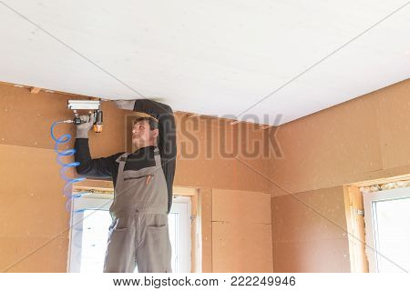 Construction worker thermally insulating eco wooden frame house with wood fiber plates. Finishing the ceiling with a white wooden board. Latvia