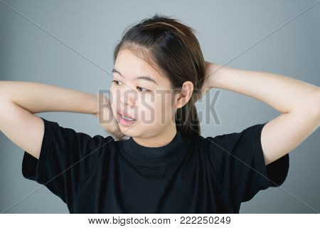 Asian girl in black casual dress catch that shoulder, Because of the pain of hard work. Or something hit the shoulder. on a gray background gives a soft light.