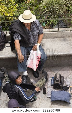 SAN JUAN OSTUNCALCO, GUATEMALA - JUNE 24: An unidentified man on a park bench gets shoe shined by an unidentified child at the San Juan Ostuncalco central park on June 24, 2017 in Guatemala.