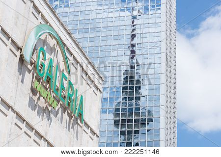 BERLIN, GERMANY - 21 MAY 2017: The Fernsehturm tower reflects on the mirror facade of the Park Inn hotel, behind the historical Galleria Kaufhof mall in Berlin, Germany.