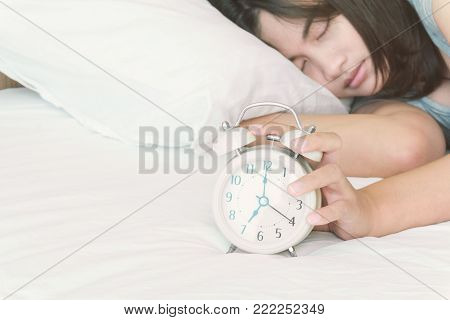 Closeup woman sleeping on the bed with alarm clock for wake up time