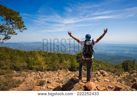 Traveler With Open Arms Stands On The Cliff, Among Green Hills