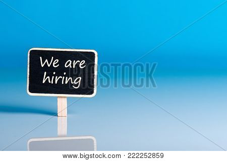 little wooden tag with message We're Hiring. Job offer open new way and give new opportunities.