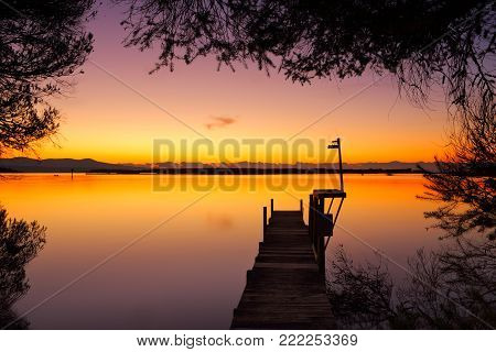 Little Old Timber Jetty On Calm Waters At Dawn And Framed By The Silhoutted Leaves Of Trees.