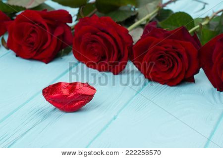Red roses and red candy lips. Close up red beautiful rose for Valentines Day with lips shaped candy, wooden background. Love and kisses.